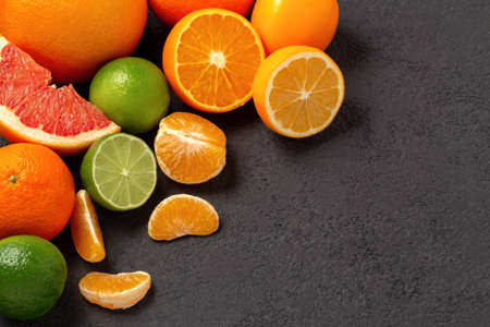group of whole and sliced citrus fruits - tangerines, lemons, limes, oranges, grapefruits on the surface of the dark table - image with copy space Banco de Imagens