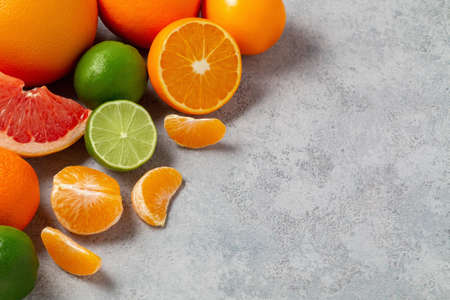 group of whole and sliced citrus fruits - tangerines, lemons, limes, oranges, grapefruits on the surface of the gray table - image with copy space Banco de Imagens