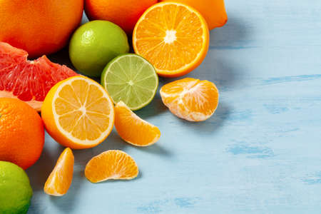 group of whole and sliced citrus fruits - tangerines, lemons, limes, oranges, grapefruits on the surface of the blue table - image with copy space