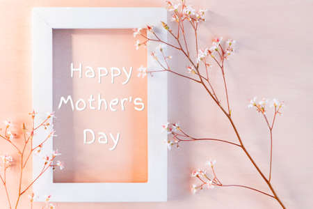 White wooden frame on a coral textured background with small flowers and the inscription Happy Mothers Day - greeting card