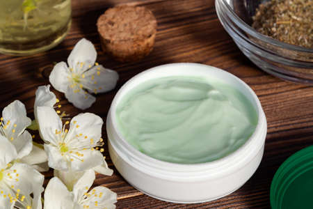 Jar of cream made from natural plant ingredients, oils and herbs, jasmine flowers on a dark wooden background - preparation of organic cosmetics concept, close up