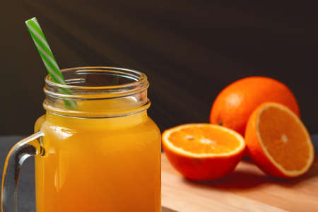 Freshly made citrus juice from oranges, grapefruit and lime in a jar-mug with a straw close up