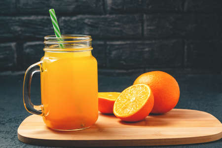 Freshly made citrus juice from oranges in a jar-mug with a straw on grey table