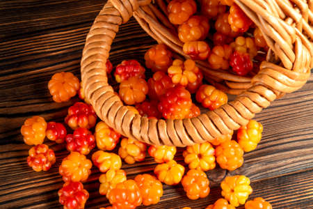 Handful of cloudberry berries poured from a small basket on an old wooden board close-up