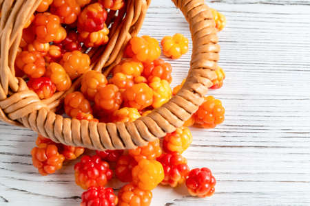 Handful of cloudberry berries poured from a small basket on an white wooden board close-up Stock Photo