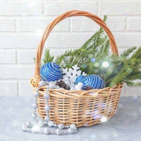 Christmas composition - wicker basket with decorations and fir branches on a light background