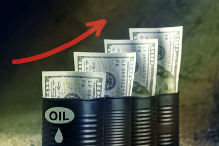 Several barrels of oil with dollars and a red arrow up - concept of higher oil prices