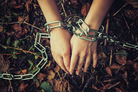 Womens hands chained in a dark forest - the concept of violence, hostage, slavery Stock Photo