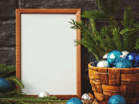 Christmas composition - a wooden frame for text and a basket with fir branches and decorations. Stock Photo