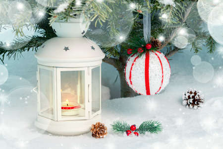 Christmas composition - a lantern with a burning candle and decorations under the Christmas tree