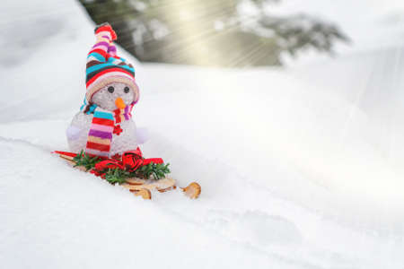 Snowman slides downhill on a sled - winter and Christmas fun concept, place for text, copy space