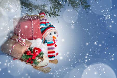 Composición navideña bajo el árbol de Navidad: un muñeco de nieve, cajas con regalos en un trineo y otras decoraciones, lugar para texto, espacio de copia