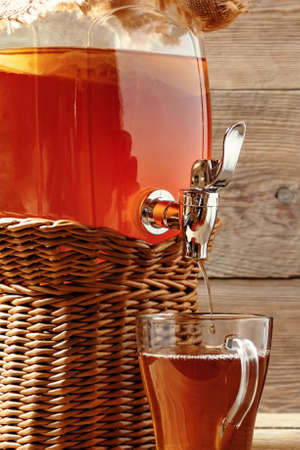 Fresh homemade Kombucha fermented tea drink in jar with faucet and in cup on wooden background. Vertical image