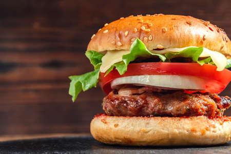 Frischer hausgemachter Burger mit Fleischkotelett, Tomaten, Salat, Käse und Zwiebeln auf einem Schieferteller auf Holzhintergrund