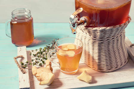 Fresh homemade kombucha fermented tea drink in a jar with faucet and in a cup and in mug on a white tray on a wooden background Imagens