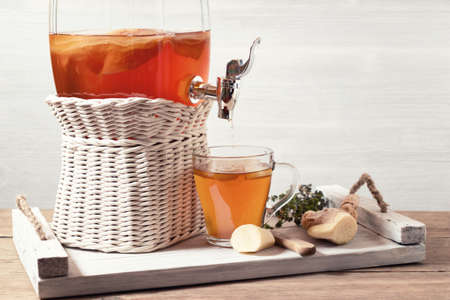 Fresh homemade kombucha fermented tea drink in a jar with faucet and in a cup on a white tray on a wooden background, copyspace.