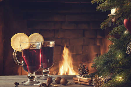 Two glasses of mulled wine on a wooden table near a Christmas tree in front of a burning fireplace