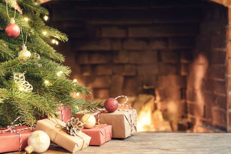 Gifts under the Christmas tree in the room with a fireplace on Christmas eve Foto de archivo