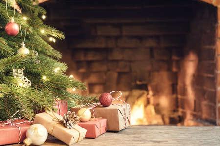 Regalos bajo el árbol de Navidad en la habitación con chimenea en Nochebuena