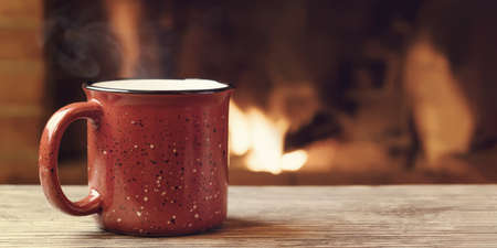 Red mug with hot tea in front of a burning fireplace, comfort, winter holidays and warmth of the hearth concept