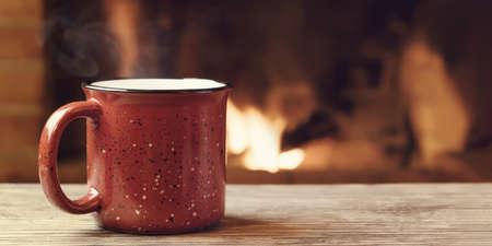 Tazza rossa con tè caldo davanti a un caminetto acceso, comfort, vacanze invernali e concetto di calore del focolare