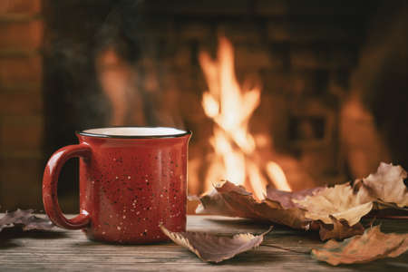 Red mug with hot tea in front of a burning fireplace, comfort and warmth of the hearth concept 免版税图像