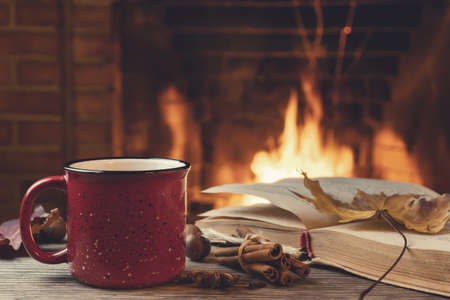 Red mug with hot tea and an open book in front of a burning fireplace, comfort, relaxation and warmth of the hearth concept.