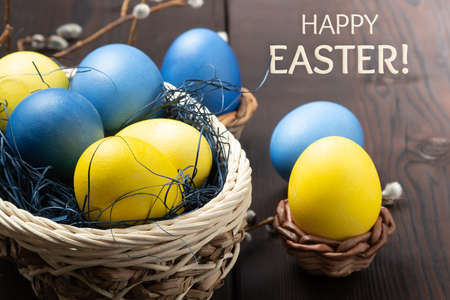 Easter greeting card - several colored eggs in a basket and on a dark wooden table with pussy-willow twigs and the inscription Happy Easter Stock Photo - 134654842