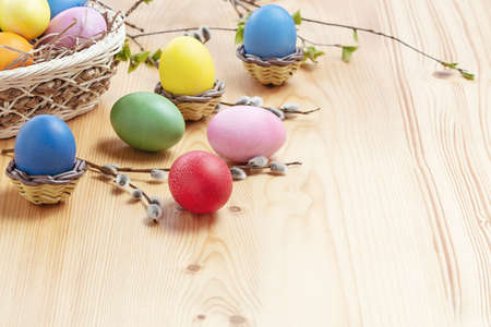 Easter composition - several colored eggs in a basket and on a light wooden table with willow twigs, place for text, copy space Stock Photo - 134654954