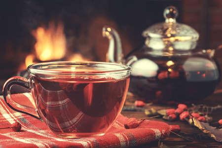 Tee mit Weißdorn in einer Glastasse und Teekanne auf einem Holztisch in einem Raum mit brennendem Kamin, Nahaufnahme Standard-Bild