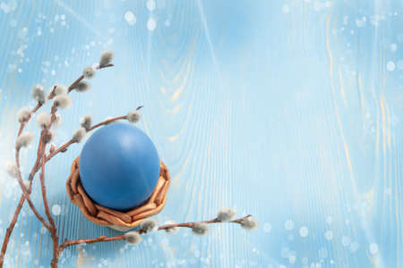 One blue egg in a wicker stand on a blue wooden table with pussy-willow twigs - blank for design or greeting card, place for text, copy space Stock fotó
