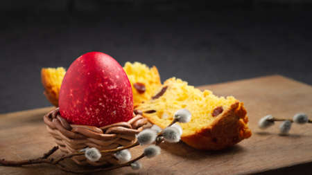 Red Easter egg in wisker stand and slice of Easter cake on a cutting board on a dark table - traditional Easter breakfast. Stockfoto