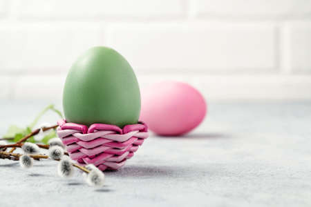 Pink and green Easter eggs in a wicker stand and on a gray table with pussy-willow twigs - Easter composition with copy space