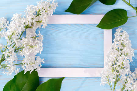 Spring or summer floral background for greeting card. White lilac and wooden frame on a blue background. Template for design with copy space