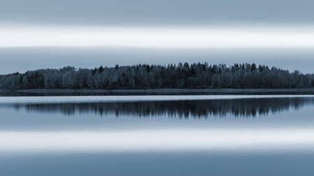 Serene landscape. Sunset on the lake, calm water surface, symmetrical reflection.