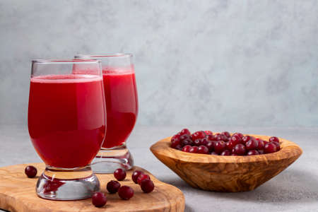 Two glasses with homemade freshly cranberry juice and a bowl of cranberries on a gray concrete table.