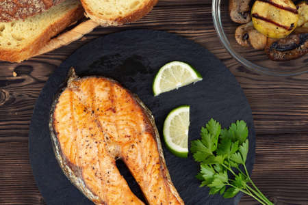 Grilled salmon steak on a black slate dish with parsley and lime