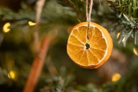 Zero waste christmas concept. Christmas tree decorated with ornaments made of natural materials - slice of dried orange and cinnamon stick, close-up Фото со стока