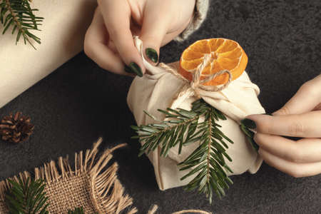 Zero waste and eco friendly christmas concept. Female hands wrap gifts in natural fabric with ornaments made of natural materials Фото со стока