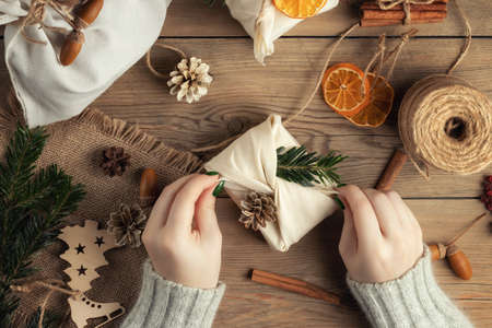 Zero waste and eco friendly christmas concept. Female hands wrap gifts in natural fabric with ornaments made of natural materials, top view, flat lay