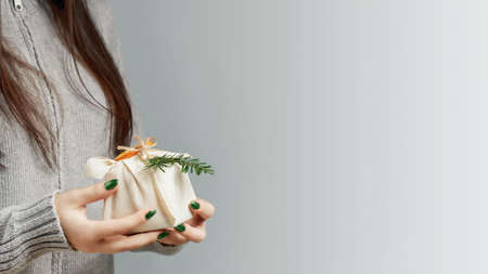 Zero waste and eco friendly christmas concept. Young woman holding in her hands a gift wrapped in natural fabric and decorated with natural materials