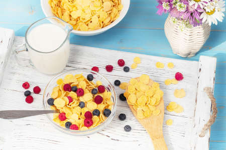 Healthy summer breakfast - cereal with milk and fresh berries in a bowl on the table. Light wooden background. Healthy eating concept
