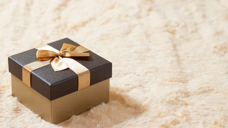 Beautiful golden box on a cream fur blanket. Surprises, gifts, discounts concept. Blank for advertising or design, copy space