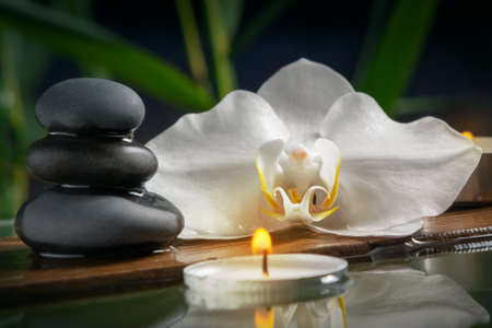 Black zen stones,candles and white orchids on a wooden plank on the surface of the water. SPA, relaxation, meditation concept