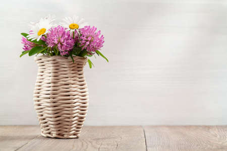 Bouquet of wildflowers, daisies and clover in a wicker vase on a wooden table. Image with copy space for postcard or design Stok Fotoğraf
