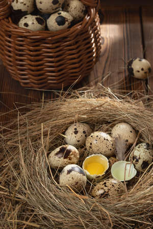 Several quail eggs in a decorative nest of straw and in a basket on a wooden table, vertical image, flatlay