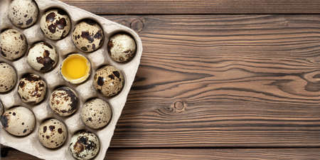 Quail eggs in cardboard packaging on a wooden table, copy space, horizontal banner