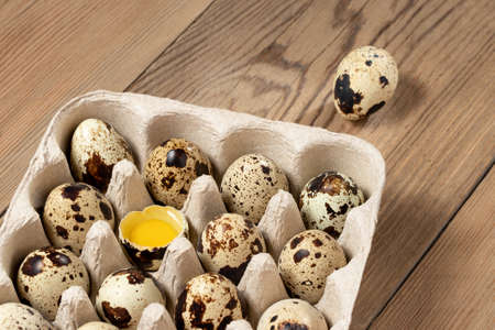 Quail eggs in cardboard packaging on a wooden table close-up