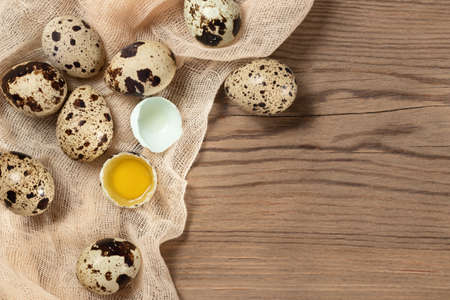 Composition of several quail eggs on decorative fabric on a wooden table, copy space, flatlay