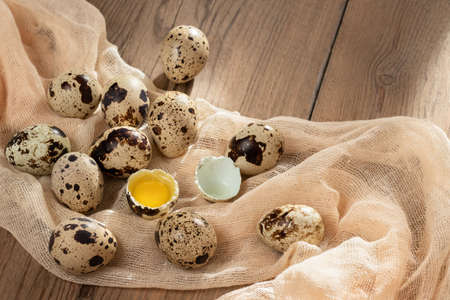 Composition of several quail eggs on decorative fabric on a wooden table close-up, flatlay Stok Fotoğraf